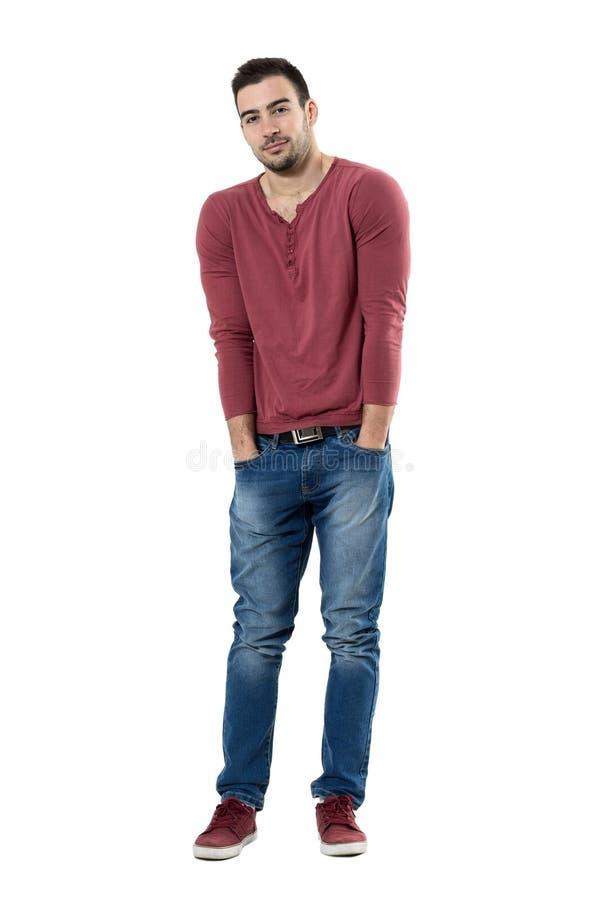 Modelo de moda joven que se inclina fresco en camisa roja del cuello en v con las manos en bolsillos en actitud tensa fotos de archivo