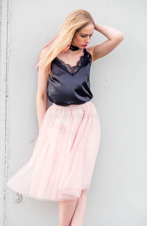 Modelo de moda de la muchacha en una falda de Tulle y un top negro que presentan contra una pared gris fotografía de archivo libre de regalías
