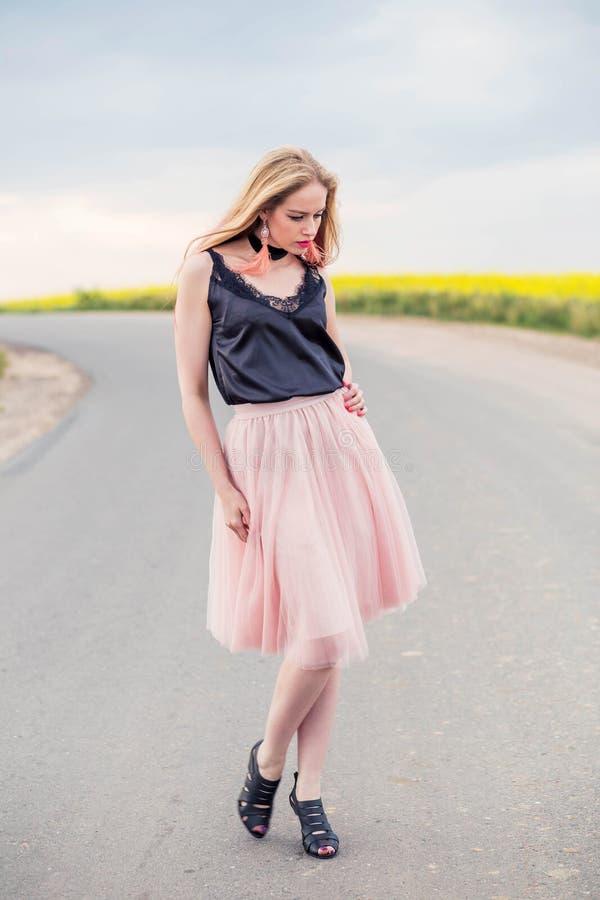 Modelo de moda de la muchacha en una falda de Tulle y un top negro que presentan en el camino fotos de archivo