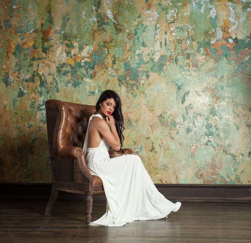 Modelo de moda lindo de la mujer en el vestido blanco en la pared verde foto de archivo