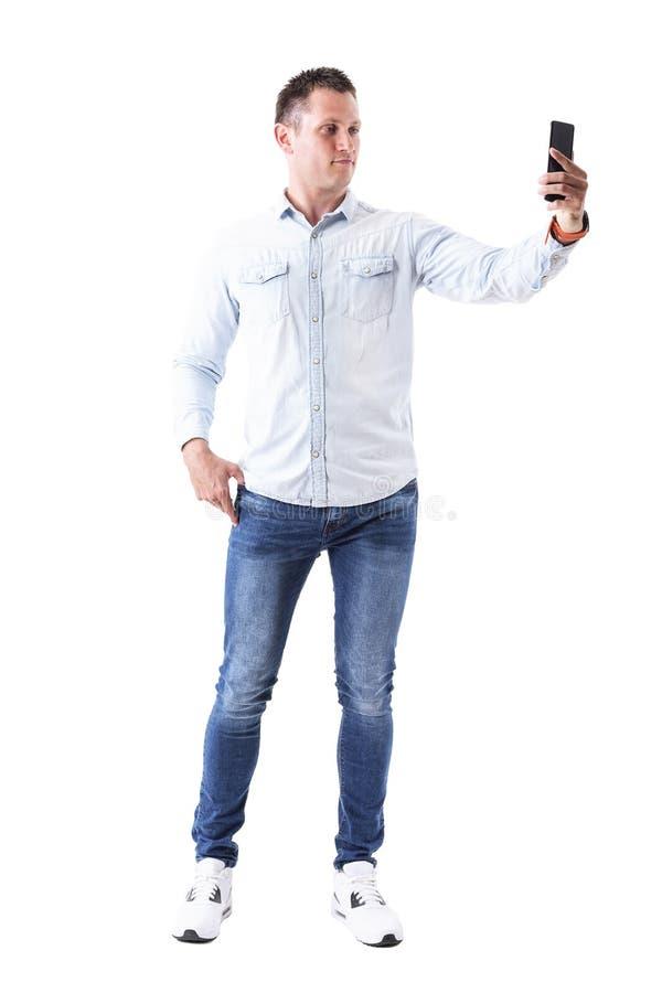 Modelo de moda masculino caucásico elegante adulto serio que toma la imagen con el teléfono móvil foto de archivo libre de regalías