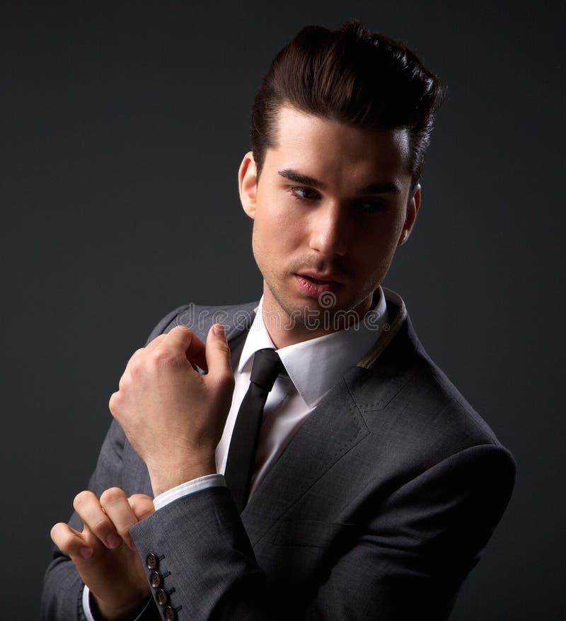 Modelo de moda masculino hermoso que presenta en traje de negocios foto de archivo