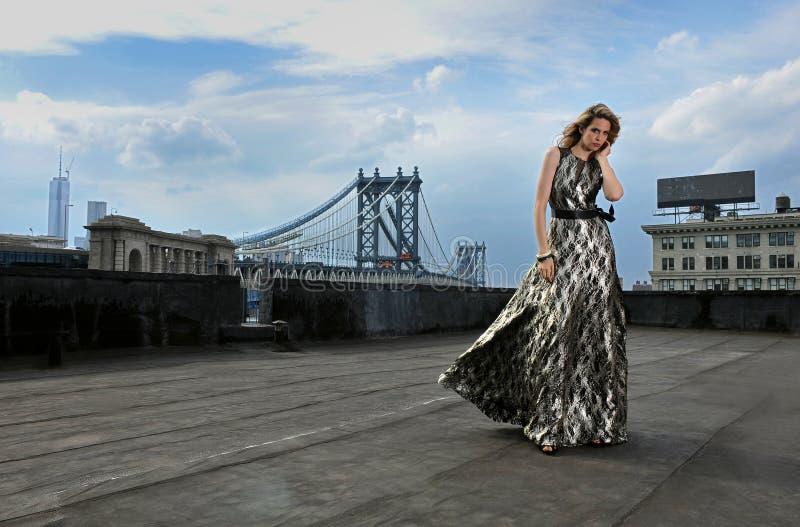 Modelo de moda que presenta el vestido de noche largo atractivo, que lleva en la ubicación del tejado foto de archivo
