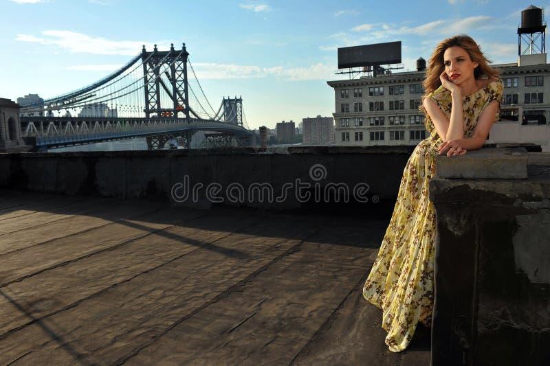 Modelo de moda que presenta el vestido de noche largo atractivo, que lleva en la ubicación del tejado foto de archivo libre de regalías