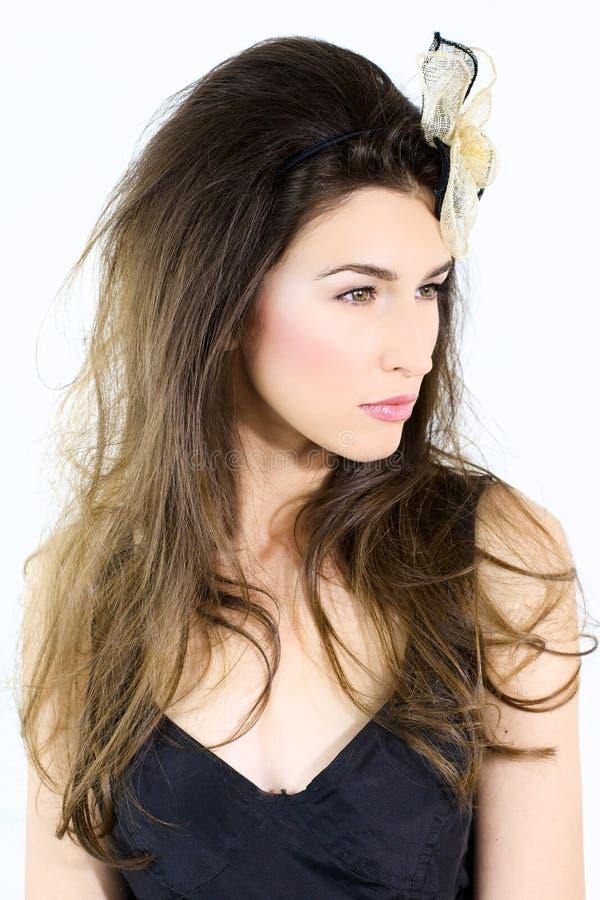 Modelo de moda serio con la flor en pelo largo imagen de archivo libre de regalías