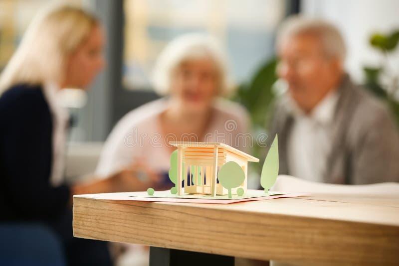 Modelo de papel de la casa en la tabla en la oficina del agente inmobiliario imagen de archivo libre de regalías