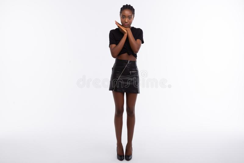 Modelo de pele escura magro com os p?s longos que vestem a saia de couro preta fotos de stock