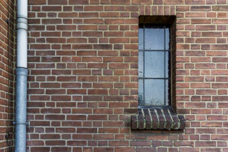 Modelo de piedra de la pared de ladrillo con un viejo marco sucio de ventana de cristal en fondo retro de la arquitectura del vit fotos de archivo libres de regalías