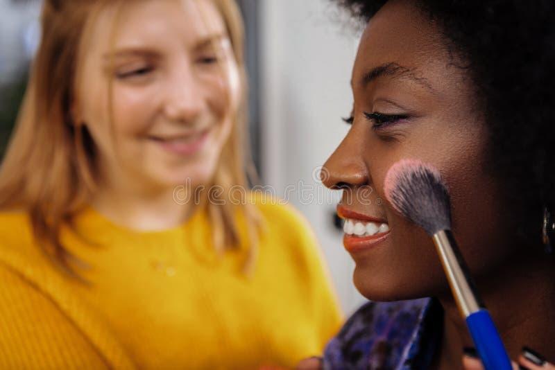 Modelo de piel morena de emisión lindo con la barra de labios coralina que parece contentada foto de archivo