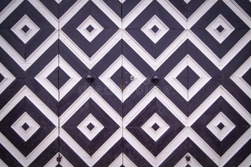 Modelo de Rhombus blancos y negros en puertas viejas foto de archivo