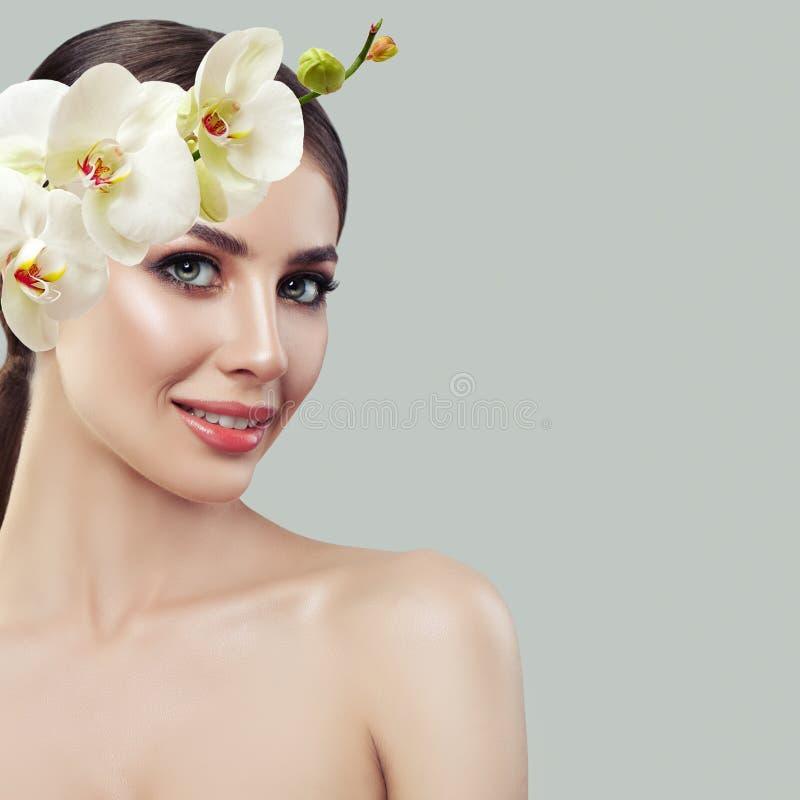 Modelo de sorriso dos termas da mulher com as flores saudáveis da pele e da orquídea fotografia de stock royalty free