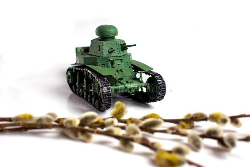 Modelo de um tanque soviético velho feito do papel em um fundo branco Ramo do salgueiro no primeiro plano imagens de stock