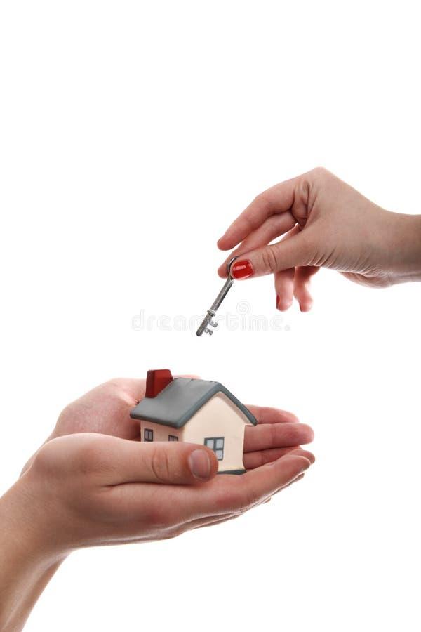 Modelo de uma casa nas mãos e na chave em outra fotos de stock royalty free