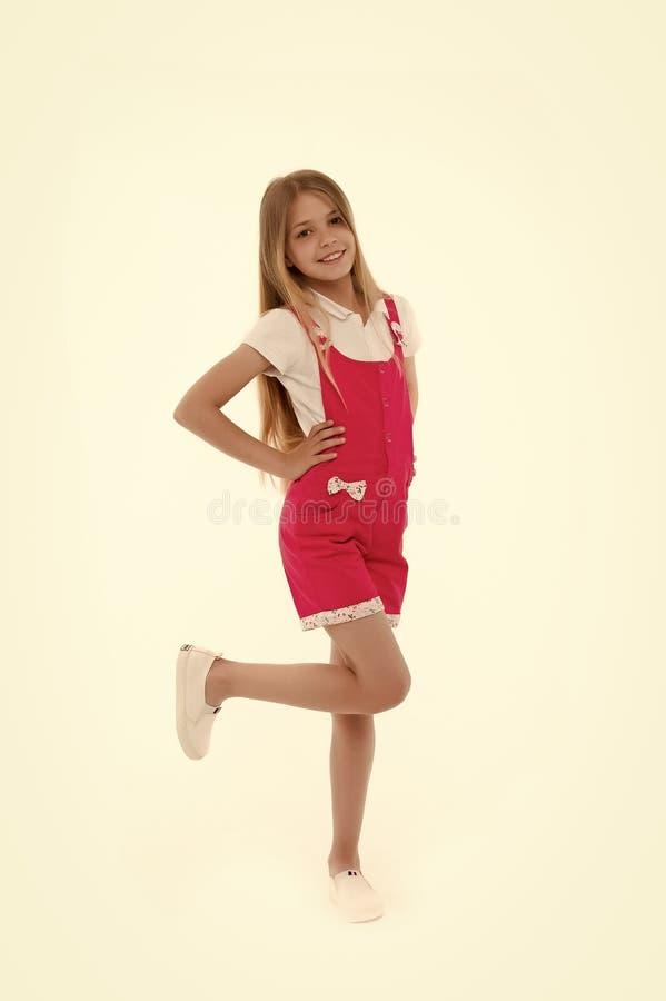 Modelo del niño en guardapolvo de moda Pequeña sonrisa de la muchacha en el mono rosado aislado en blanco Niño que sonríe con rub fotos de archivo
