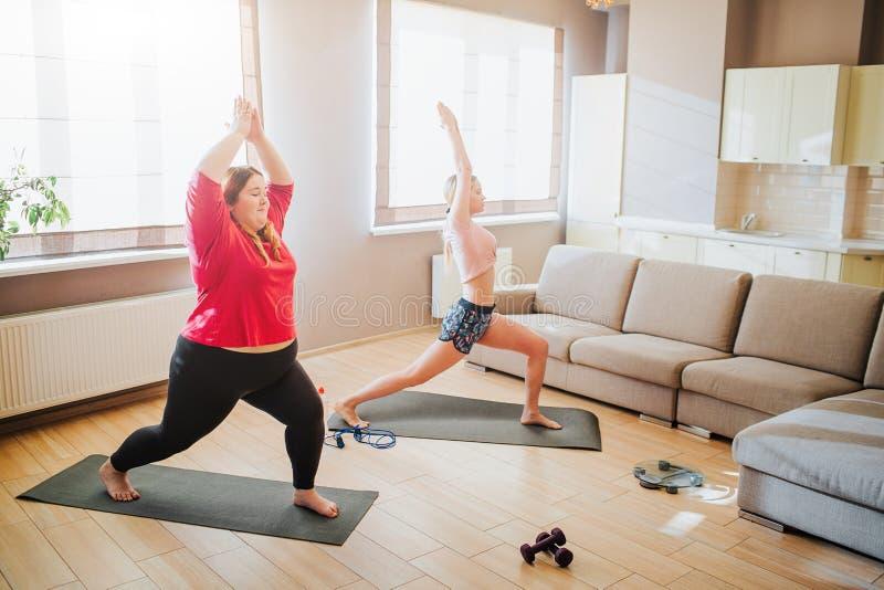 Modelo del tamaño extra grande de Youbng y mujer bien hecha que hacen ejercicio junto El estirar para arriba y colocación en acti imagenes de archivo