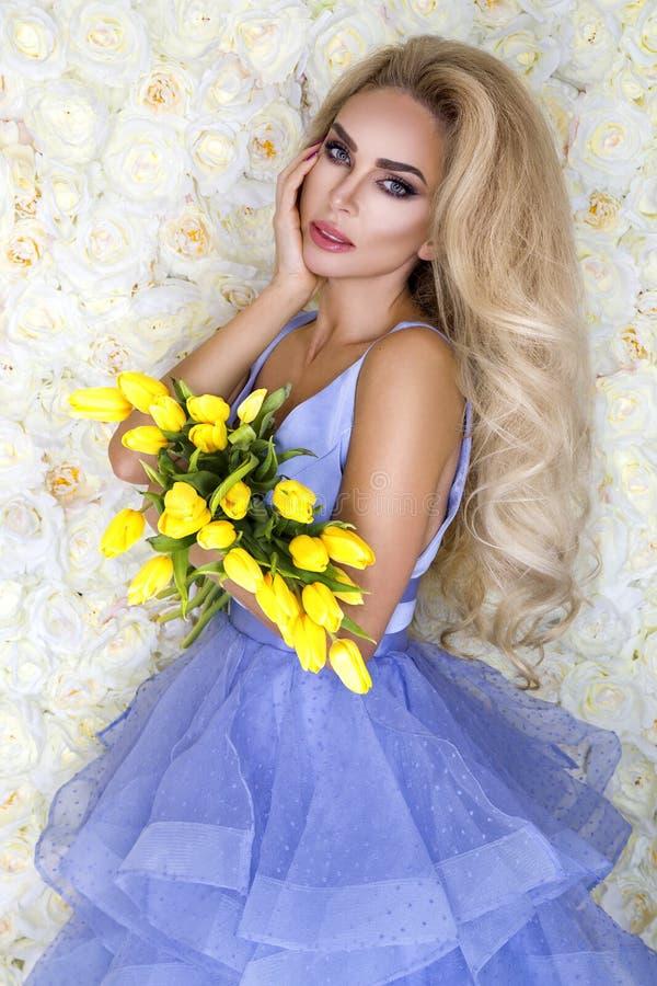Modelo del vestido de boda de la moda con un ramo de tulipanes Modelo hermoso de la novia en vestido que se casa asombroso azul M foto de archivo
