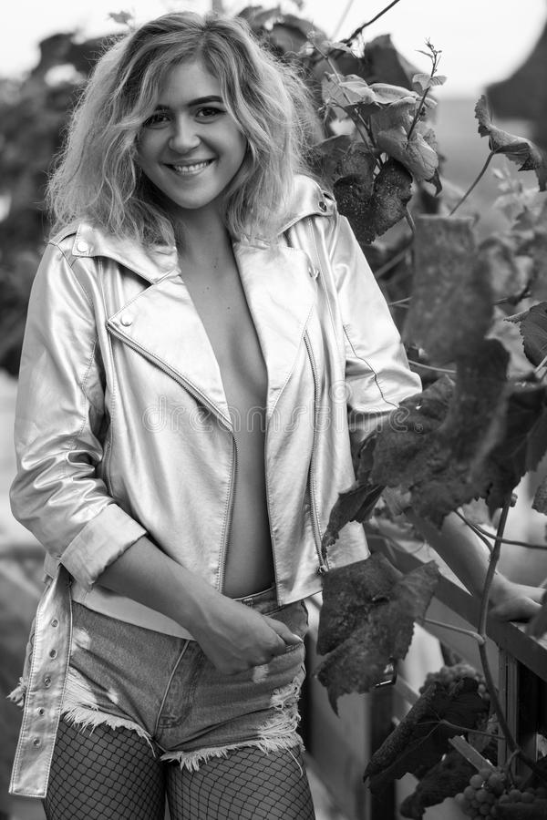 Modelo delgado joven en la ropa atractiva que presenta en arbustos de la uva imagenes de archivo