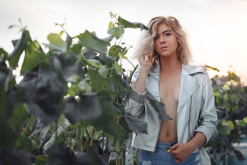 Modelo delgado joven en la ropa atractiva que presenta en arbustos de la uva fotos de archivo libres de regalías