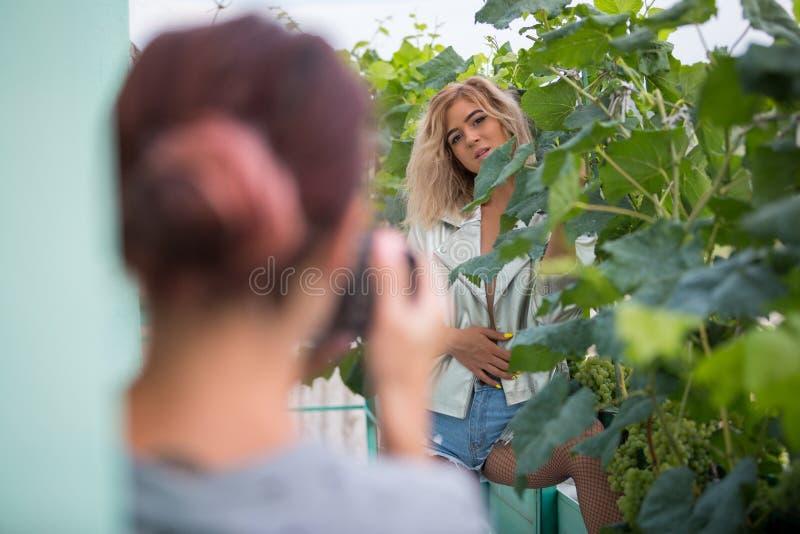 Modelo delgado joven en la ropa atractiva que presenta en arbustos de la uva Ella ` s que es fotografiado por una muchacha fotografía de archivo