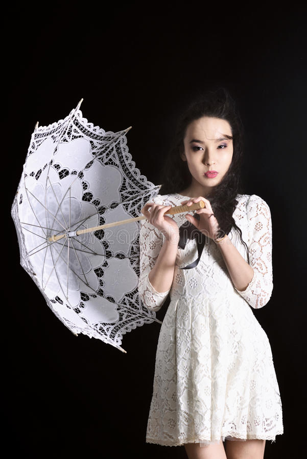 Modelo delgado joven en vestido ligero del verano con un paraguas afiligranado que presenta en estudio Fondo negro imagen de archivo libre de regalías