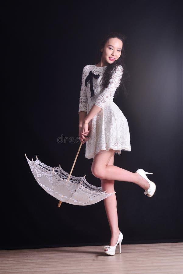 Modelo delgado joven en vestido ligero del verano con un paraguas afiligranado que presenta en estudio Fondo negro foto de archivo libre de regalías