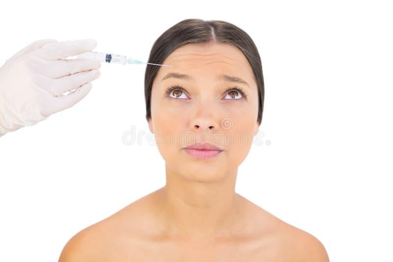 Modelo desnudo preocupante teniendo inyección del botox en la frente imagen de archivo libre de regalías