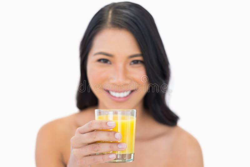 Modelo desnudo sensual sonriente que bebe el zumo de naranja fotos de archivo libres de regalías