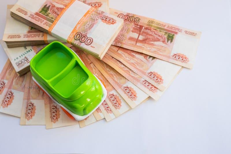 Modelo diminuto do carro e balanço financeiro com papel moeda, moeda de papel Finança e empréstimo automóvel, dinheiro de salvame imagens de stock