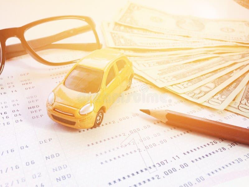 Modelo diminuto do carro, lápis, monóculos, caderneta bancária do dinheiro e de conta poupança ou balanço financeiro no fundo bra fotografia de stock