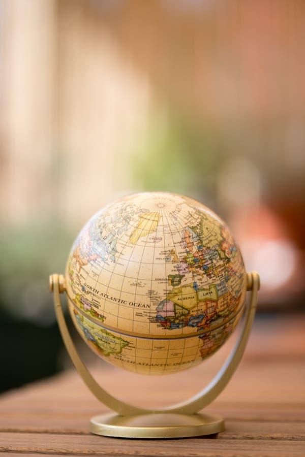 Modelo diminuto do globo em uma tabela de madeira rústica Símbolo para viajar imagens de stock royalty free