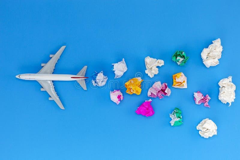 Modelo do avião com a vária bola de papel no fundo azul com espaço da cópia Preparação para o conceito da viagem e da excursão foto de stock