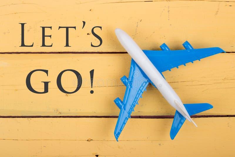 Modelo do avião e do texto Let' s vai! no fundo de madeira amarelo foto de stock royalty free