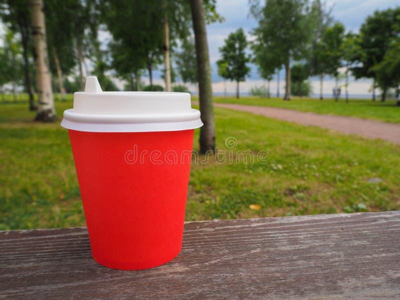 Modelo do copo de café afastado de papel vermelho na superfície de madeira no fundo do parque do verão, para a montagem da exposi fotografia de stock royalty free