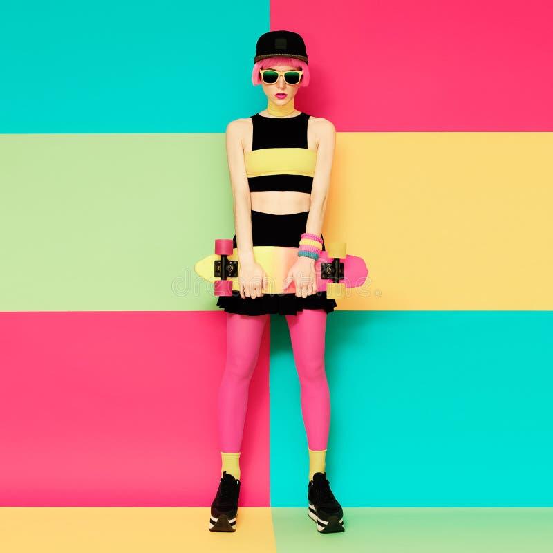 Modelo do encanto com o skate no fundo exclusivo brilhante foto de stock