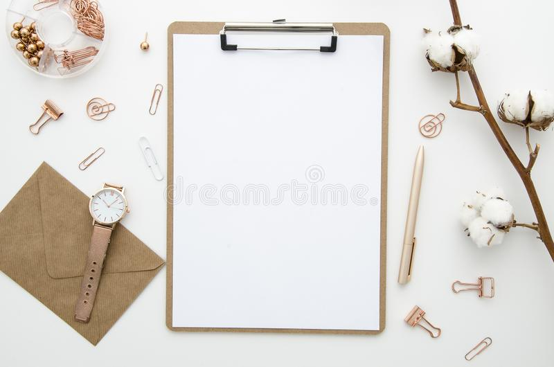 Modelo do espaço de trabalho do escritório domiciliário com envelope, placa de grampo, flores do algodão e os acessórios dourados foto de stock