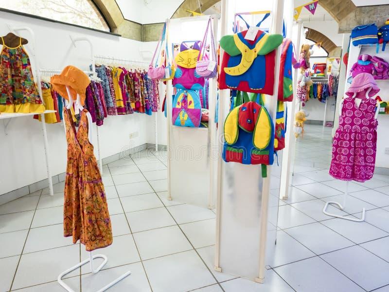 Modelo do fantoche na loja de pano com os sacos da roupa e do algodão da criança, na roupa moderna da forma e nos acessórios, sup fotografia de stock