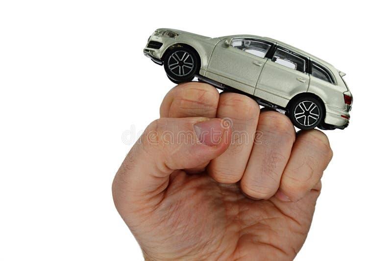 Modelo do grande carro colorido metálico de prata de SUV colocado no punho aumentado da pessoa masculina adulta, fundo branco fotografia de stock