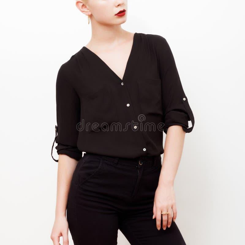 Modelo do moderno swag Estilo m?nimo Encanto do vintage Modelo elegante em uma camisa de seda na moda e em umas calças pretas equ fotos de stock