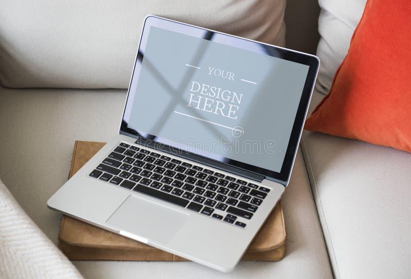 Modelo do monitor do portátil no sofá fotografia de stock
