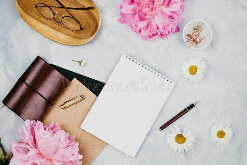 Modelo do negócio com fontes dos artigos de papelaria, margaridas, flores da peônia, cadernos e vidros fotografia de stock