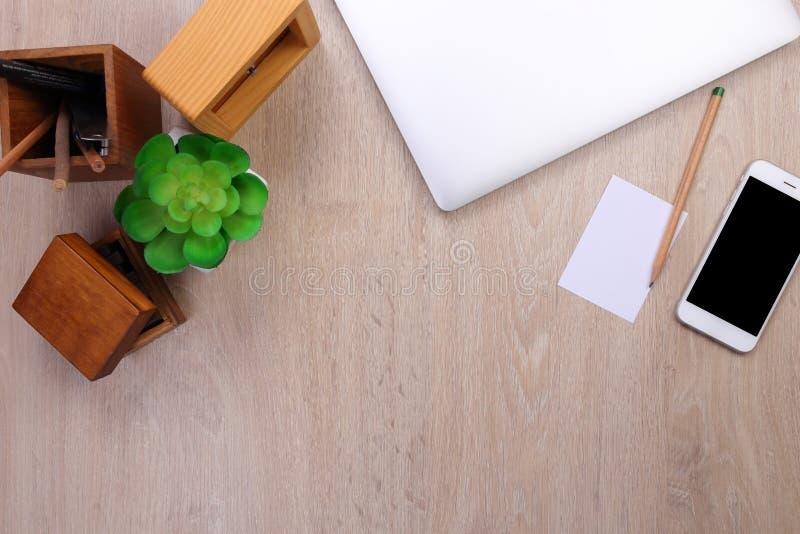Modelo do portátil da vista superior, smartphone e artigos de papelaria do escritório com fundo de madeira imagem de stock