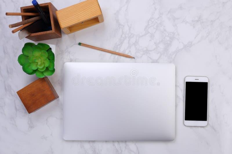 Modelo do portátil da vista superior, smartphone e artigos de papelaria do escritório no fundo de mármore fotografia de stock