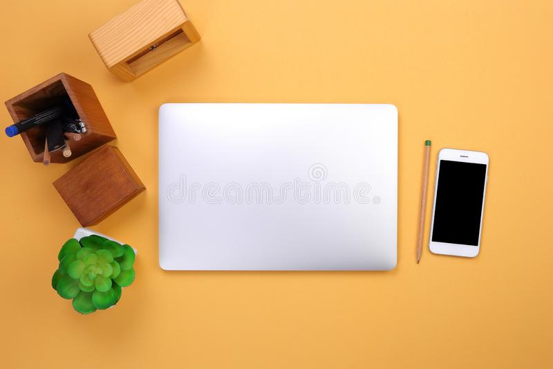 Modelo do portátil da vista superior, smartphone e artigos de papelaria do escritório no fundo pastel foto de stock royalty free