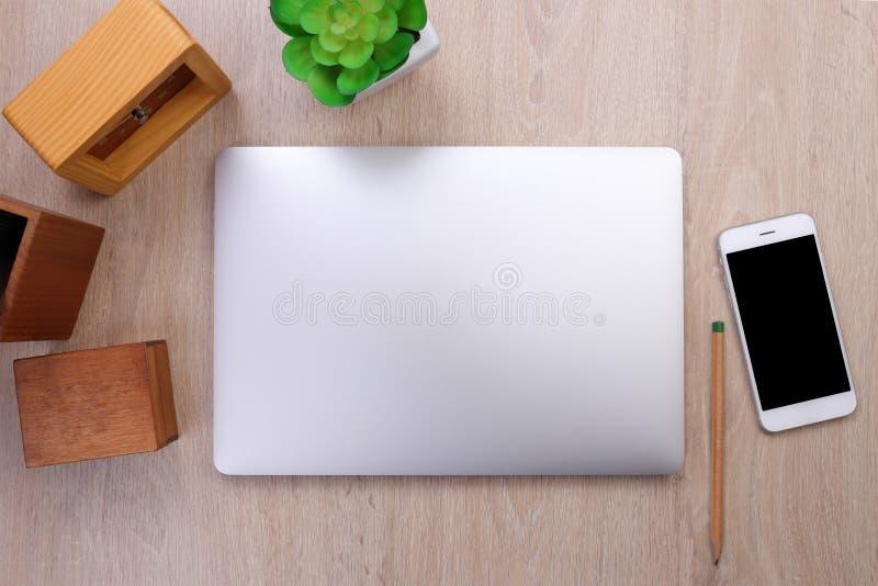 Modelo do portátil, smartphone e artigos de papelaria do escritório no fundo de madeira fotos de stock