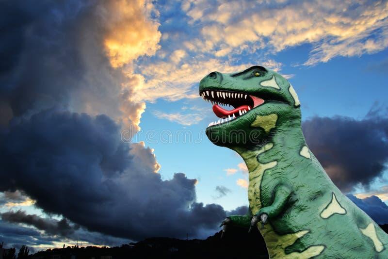Modelo do tiranossauro-rex contra um céu do por do sol com nuvens de tempestade imagem de stock