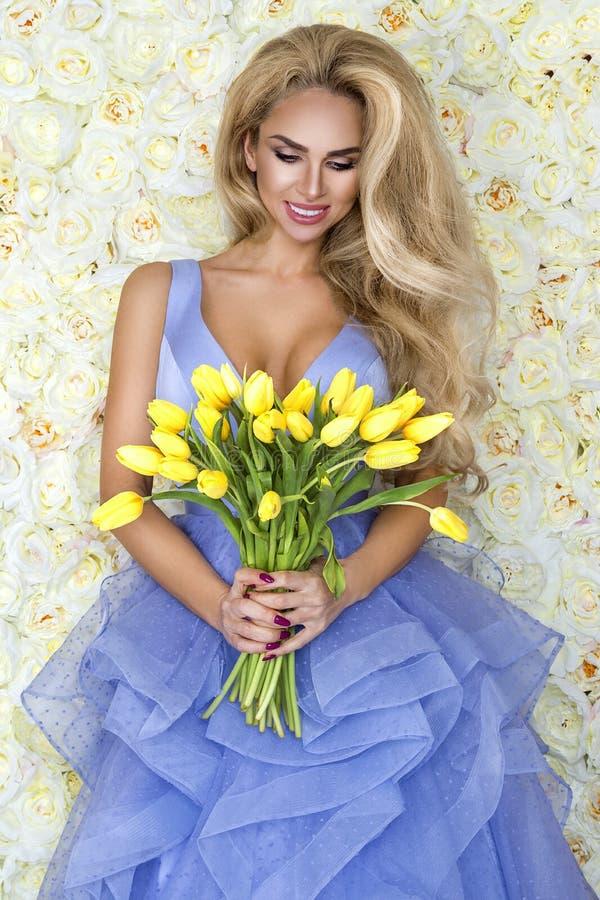 Modelo do vestido de casamento da forma com um ramalhete das tulipas Modelo bonito da noiva no vestido de casamento surpreendente foto de stock royalty free