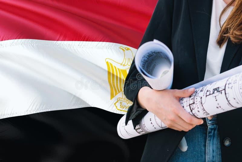 Modelo egípcio da terra arrendada da mulher do arquiteto contra o fundo de ondulação da bandeira de Egito Conceito da constru??o  imagens de stock