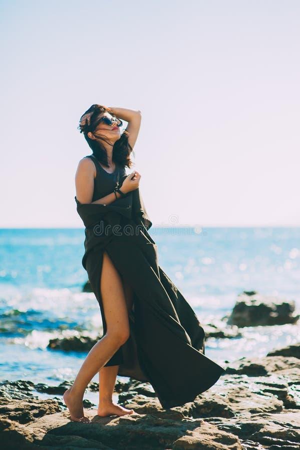 Modelo elegante bonito na praia no vestido longo bonito fotografia de stock