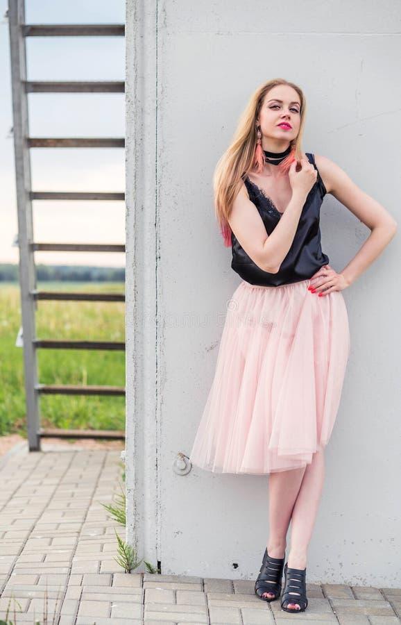 Modelo elegante da menina em uma saia do tule e em uma parte superior preta que levantam contra uma parede cinzenta imagem de stock