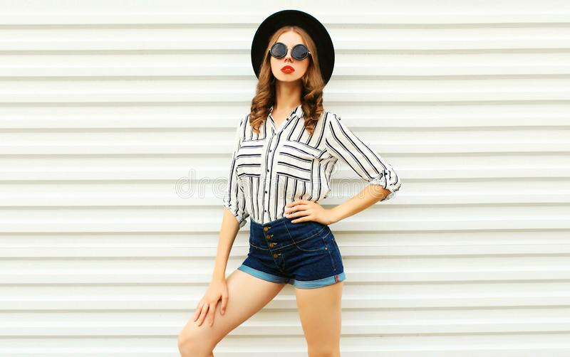 Modelo elegante de la mujer joven en el sombrero redondo negro, pantalones cortos, camisa rayada blanca que presenta en la pared  imágenes de archivo libres de regalías